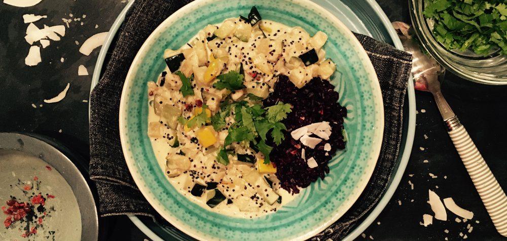 Zucchini in Kokosmilch auf schwarzem Reis